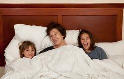 母亲和两个女儿在床上 库存照片