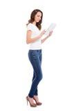 举行片剂估计的时髦的牛仔裤的一个年轻和愉快的女孩 免版税库存图片