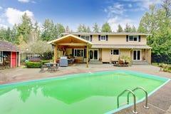 有游泳池和露台区域的美丽的后院 免版税图库摄影