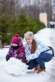有使用与雪的女儿的微笑的母亲在冬天公园 免版税库存图片