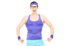 显示肌肉的运动服的年轻人 免版税库存照片
