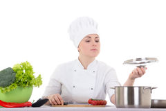 在白色隔绝的制服烹调的年轻可爱的厨师妇女 免版税库存照片