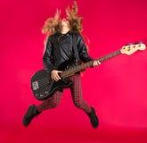 有低音吉他跃迁的白肤金发的摇滚乐女孩在红色 免版税库存图片