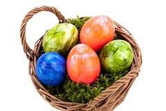 Καλάθι των λαμπρά χρωματισμένων αυγών Πάσχας Στοκ Φωτογραφία