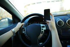 送文本的女实业家的特写镜头,当驾驶时 免版税库存图片