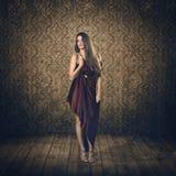 美好的模型在红色丝绸礼服和葡萄酒背景中 库存图片