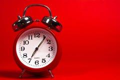 Ένα κόκκινο εκλεκτής ποιότητας ξυπνητήρι σε ένα κόκκινο υπόβαθρο Στοκ εικόνα με δικαίωμα ελεύθερης χρήσης