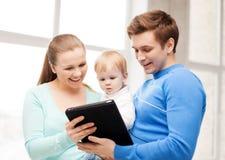 父母和可爱的婴孩有片剂个人计算机的 库存照片