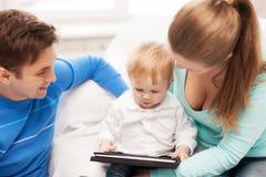 父母和可爱的婴孩有片剂个人计算机的 免版税库存照片