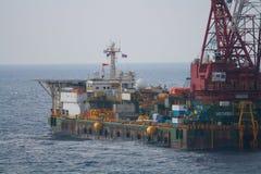 安装平台的大起重机船近海处,做海洋抬举费力的设施的起重机驳船在海湾运转 免版税库存照片