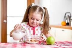Παιδί που προετοιμάζει τις νιφάδες καλαμποκιού με το γάλα Στοκ φωτογραφία με δικαίωμα ελεύθερης χρήσης