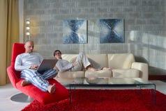 使用便携式计算机的年轻夫妇在家 免版税库存照片