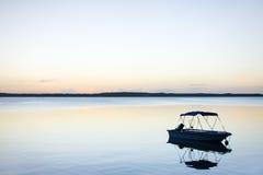 一条小船的剪影在日落的 库存图片