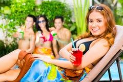 集会在池边聚会的亚裔朋友在旅馆里 免版税库存照片