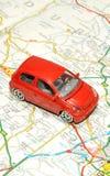 Μικρό αυτοκίνητο παιχνιδιών στον οδικό χάρτη Στοκ Φωτογραφίες
