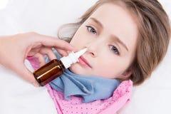 Μικρό κορίτσι με το κακό κρύο που χρησιμοποιεί τις ρινικές πτώσεις. Στοκ εικόνα με δικαίωμα ελεύθερης χρήσης