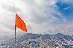 与雪山的红旗 免版税库存照片
