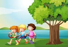 使用与绳索的三个孩子在河附近 库存图片