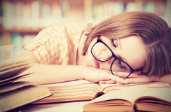 戴眼镜的疲乏的学生女孩睡觉在书的在图书馆里 库存图片