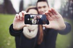 采取自画象的逗人喜爱的年轻夫妇 免版税库存照片