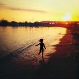 跑在海滩的无忧无虑的孩子 免版税库存照片