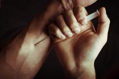 有海洛因注射器的手 免版税库存图片