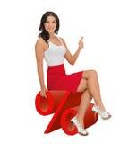 妇女坐大红色百分号 免版税库存图片