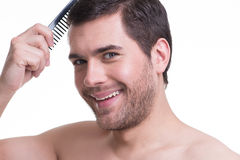 梳头发的愉快的年轻人。 免版税库存照片