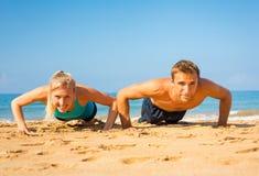做在海滩的夫妇俯卧撑 免版税库存图片