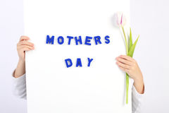 拿着有蓝色文本母亲节和一的两只童年手白板白色和紫罗兰色郁金香 库存图片