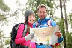 远足看地图的夫妇远足在森林里 免版税库存照片