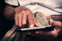 演奏片剂的老人 免版税库存图片