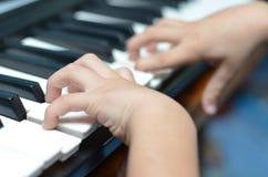 演奏键盘特写镜头的小孩手 免版税库存照片