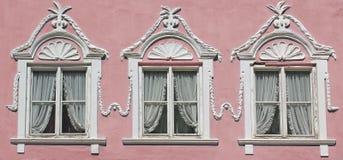 在桃红色房子墙壁上的三个窗口有华丽的灰泥的 免版税图库摄影