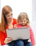 愉快的母亲和女儿有便携式计算机的 库存照片