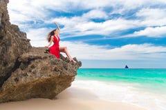 红色礼服的年轻美丽的单独妇女坐岩石 库存照片