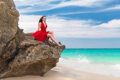 红色礼服的年轻美丽的单独妇女坐岩石 免版税库存图片