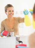 微笑的主妇清洁镜子在卫生间里 图库摄影