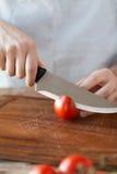 男性手切口蕃茄在船上与刀子 免版税图库摄影