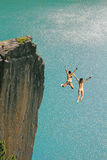 Δύο πηδώντας κορίτσια απότομων βράχων, ενάντια στον τυρκουάζ ωκεανό Στοκ Εικόνες