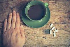 食用的人药片和咖啡 免版税库存图片