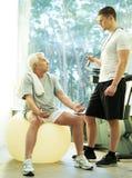 老人和教练员在健身俱乐部 免版税库存图片