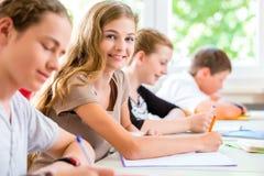 写测试的学生在学校集中 免版税库存照片