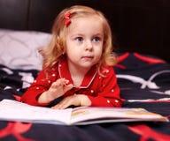 读书的逗人喜爱的女孩在床 免版税库存图片