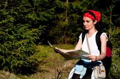 有一张地图的妇女在森林里 免版税库存照片