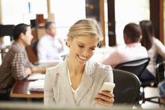 工作在书桌的女实业家使用手机 免版税库存图片