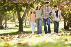 走通过秋天森林地的家庭 库存图片