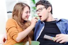 给食物的美丽的少妇她的电视的亲爱的前面 免版税图库摄影