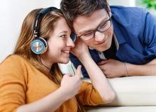 有吸引力的年轻夫妇听的音乐一起在他们的生活 免版税库存图片