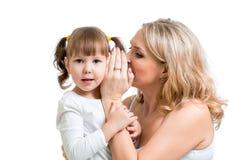 分享一次秘密耳语的母亲和孩子 免版税库存照片